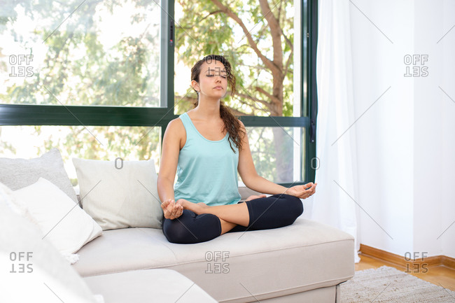 Concentrated flexible female sitting with crossed legs and mudra hands on sofa and doing yoga in Padmasana while practicing mindfulness with closed eyes