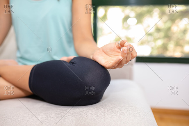 Crop flexible female sitting with crossed legs and mudra hands on sofa and doing yoga in Padmasana while practicing mindfulness with closed eyes