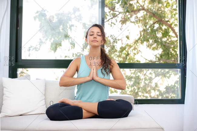 Concentrated flexible female sitting with crossed legs doing yoga in Padmasana while practicing mindfulness with closed eyes
