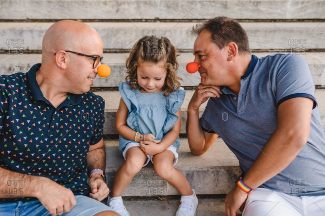 Side view of cheerful homosexual male couple with adopted little girl having fun and playing with colorful clown noses