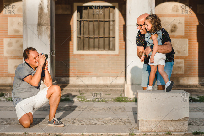 Side view of smiling gay man with photo camera taking picture of delighted father and daughter hugging and standing on street on sunny day