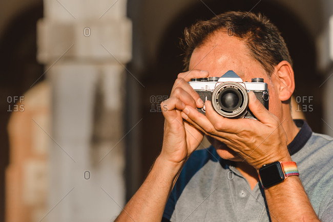 Unrecognizable male photographer covering face with retro photo camera and taking photo on sunny day on street