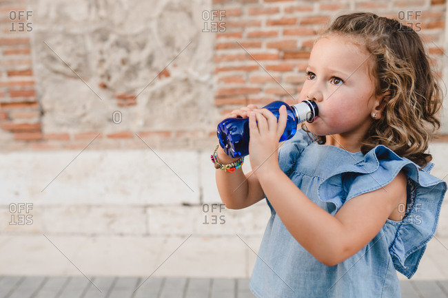Adorable child standing on street and enjoying fresh water from plastic bottle during city stroll while looking away