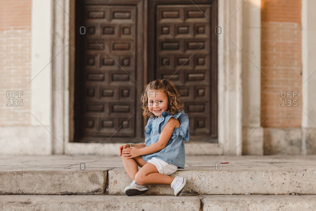 Positive little child in summer outfit sitting with raised arm on stairs on street and looking at camera while enjoying stroll