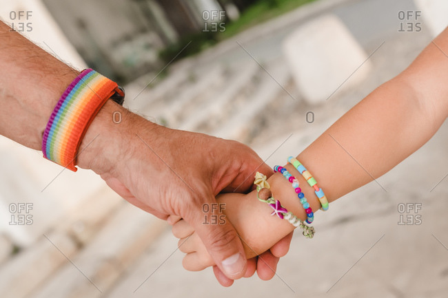 Unrecognizable crop gay man with rainbow bracelet holding hand of little kid while standing together in city at weekend
