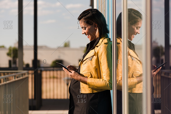 Side view of delighted pregnant female leaning on glass building in city and chatting on social media via cellphone