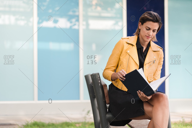 Pensive female sitting on bench in urban park and enjoying interesting story in book while relaxing at weekend in city