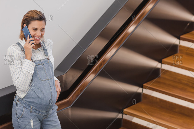 Content pregnant female leaning on railing and having conversation on smartphone while standing near staircase in modern building