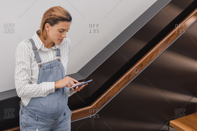 Concentrated pregnant female in denim overalls standing near staircase in contemporary building and surfing Internet via cellphone