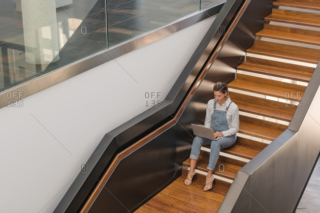 High angle of female freelancer sitting on wooden staircase in modern building and working on project while using netbook