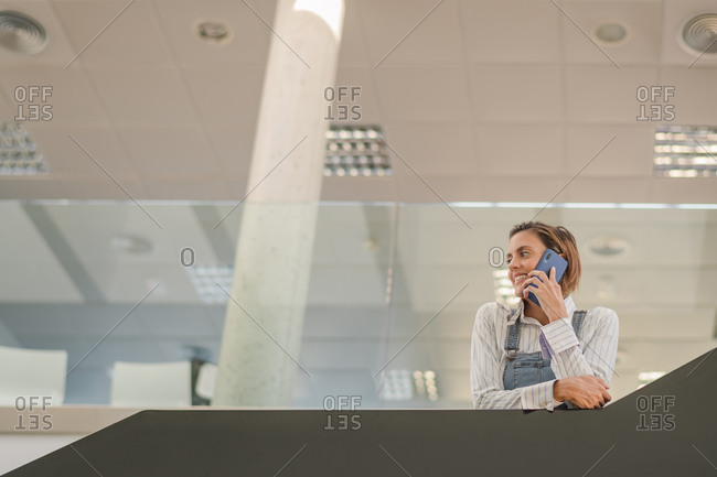 From below of busy female employee standing in contemporary office lounge and speaking about project while working and looking away