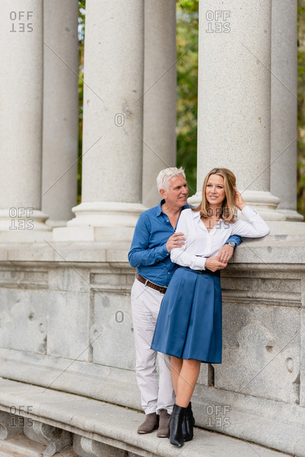 Delighted man standing near stone border and tenderly embracing woman leaning on fence during stroll in park