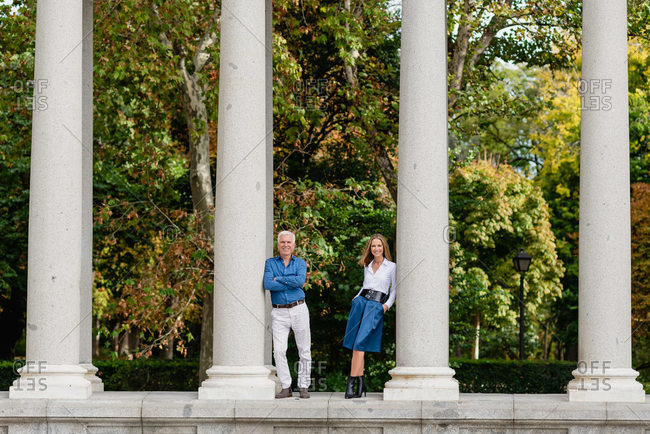 Remote view of couple leaning on stone columns of arched passage in urban park during summer stroll
