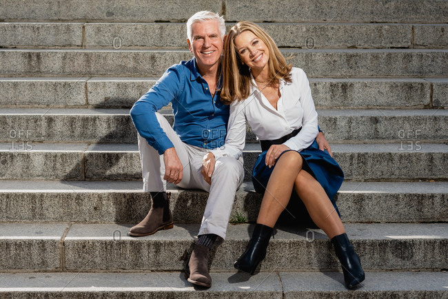 Mature couple in love sitting on stone steps in city and leaning on each other while looking at camera and enjoying stroll at weekend