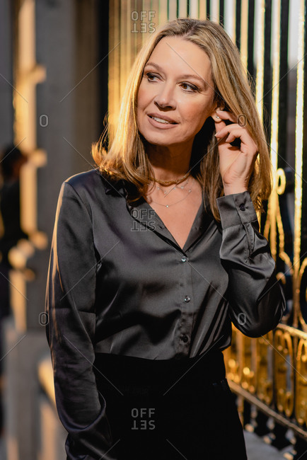 Positive confident middle aged lady in classy wear touching ear and looking away while standing against blurred metal fence on street