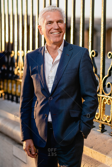 Happy gray haired senior executive male in elegant blue suit standing near metal fence and looking away