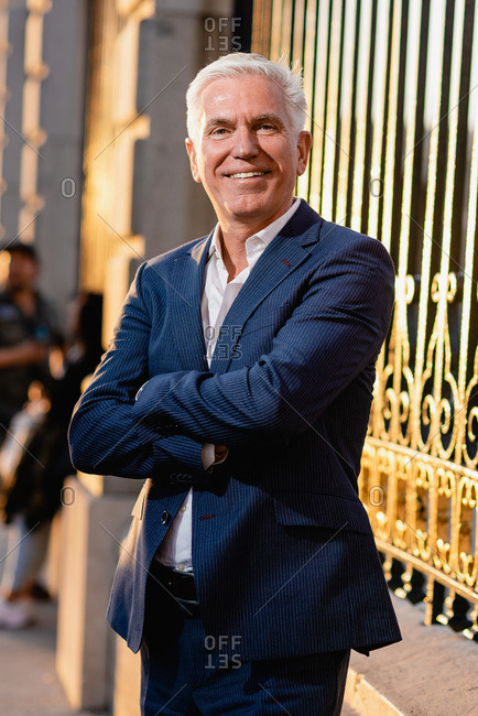 Happy gray haired senior executive male in elegant blue suit standing with arms crossed near metal fence and looking at camera