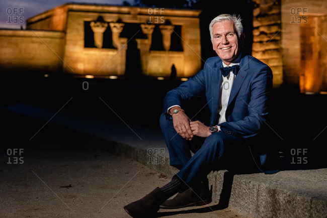 Positive elegant senior male in stylish blue suit with bow tie and wristwatches sitting on stone border in night city and looking at camera