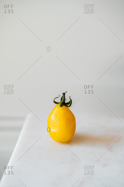 High angle of fresh whole ripe yellow tomato with green leaves placed on white table