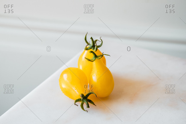 High angle of whole and cut ripe yellow tomatoes placed on white table with fresh green herbs
