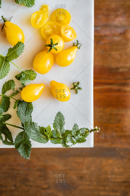 Whole and cut ripe yellow tomatoes placed on white table with fresh green herbs