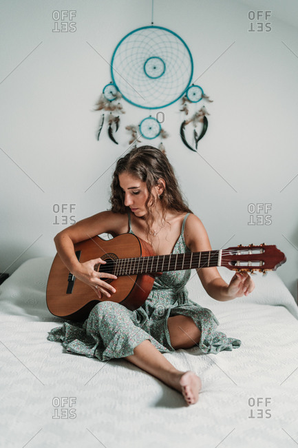 Female guitarist sitting on cozy bed at home and playing acoustic musical instrument with closed eyes