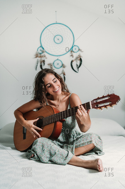 Cheerful ethnic female guitarist sitting on cozy bed at home and playing acoustic musical instrument with closed eyes