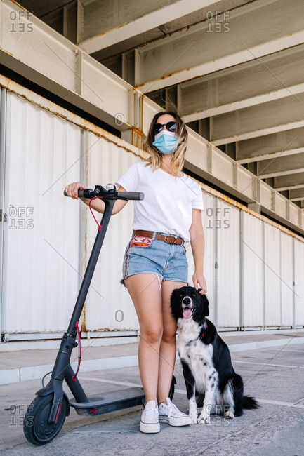 Teen female in sunglasses and protective mask standing near electric scooter and stroking dog on parking lot