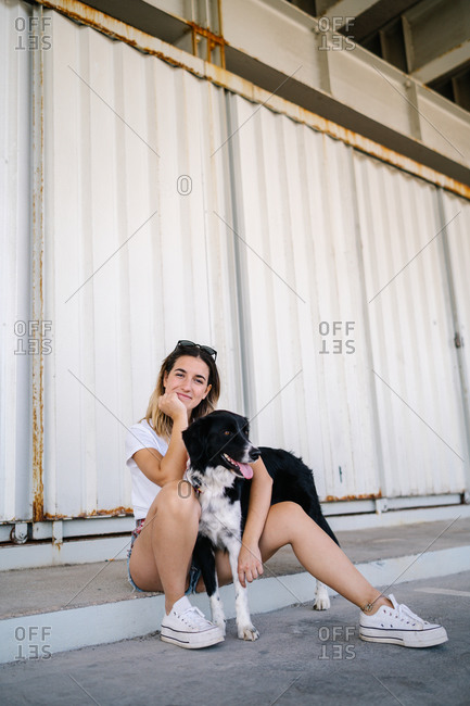 Full body side view of young female in casual outfit sitting with big dog near metal wall of urban building