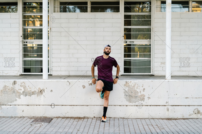 Determined athletic male in running clothes standing near stone fence on street during training and looking at camera