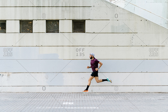 Side view of active sportsman in moment of running along pavement in city during dynamic training