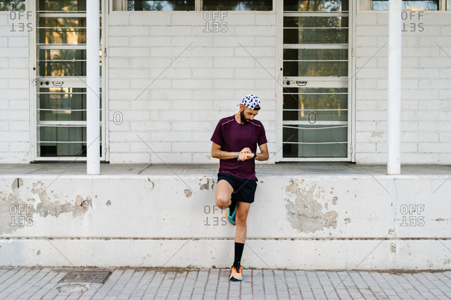 Determined athletic male in running clothes standing checking time on wristwatch near stone fence on street during training