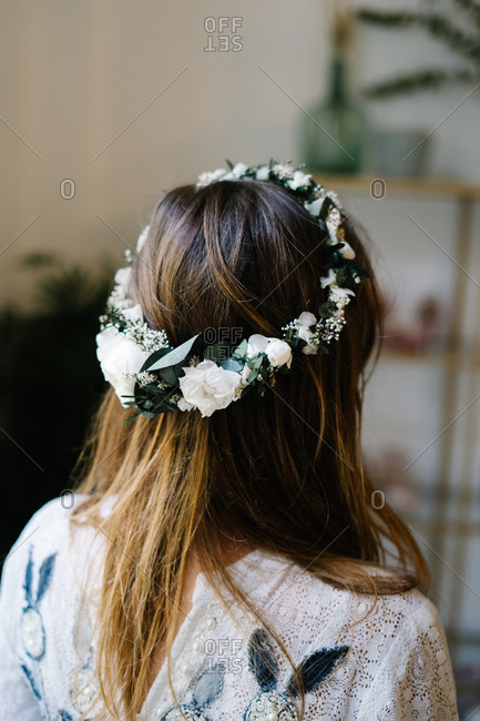 Back view of anonymous female wearing tender wreath with white rose flowers standing in flat