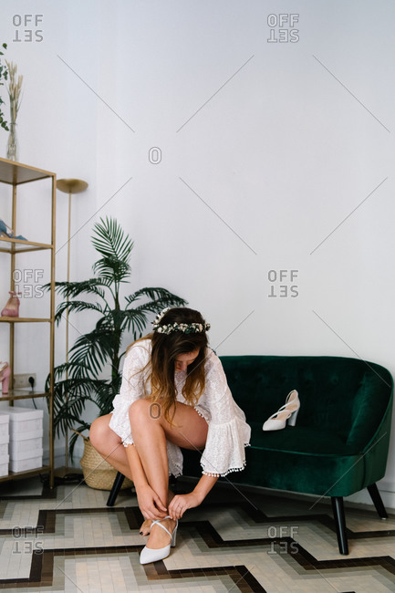 Graceful female in delicate white dress and with floral wreath in hair sitting on sofa and putting on trendy high heeled shoes