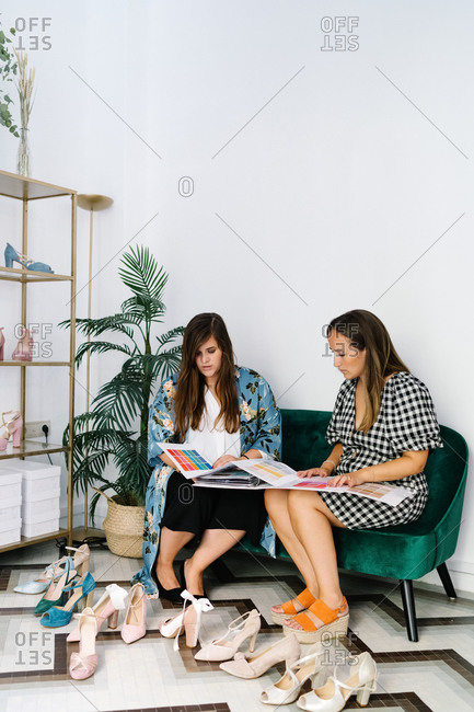 Busy female designers sitting on sofa in expensive boutique with new collection of trendy high heeled shoes