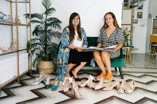Busy female designers sitting on sofa and looking at camera in expensive boutique with new collection of trendy high heeled shoes