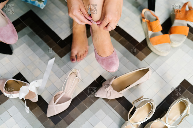 From above of unrecognizable crop female sitting in luxury boutique surrounded by pairs of various footwear and putting on elegant high heels