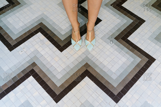 High angle of anonymous female wearing elegant trendy high heeled shoes standing in boutique