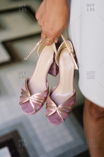 High angle of crop anonymous female standing with pair of elegant high heeled shoes on blurred background of floor in shop