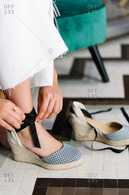 Crop view of anonymous woman sitting on sofa and putting on trendy high heeled shoes