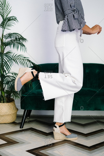Side view of anonymous crop female wearing wedge sandals and trendy jeans standing with raised leg in modern flat