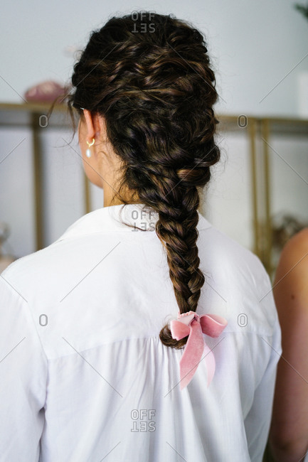 Back view of unrecognizable female with tender braid with ribbon standing in bright hairstyle salon