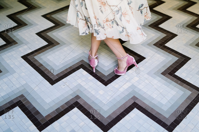 High angle of unrecognizable female wearing elegant dress and stylish high heeled shoes turning around on floor in luxury boutique