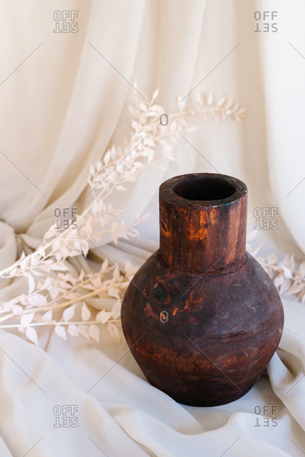 Old handmade clay vase placed on piece of fabric with dried plant in studio
