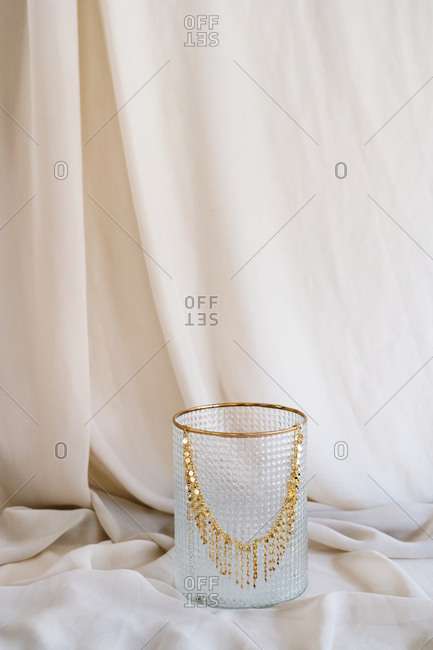 Elegant shiny necklace made of gold placed on glass stand on piece of cloth in studio