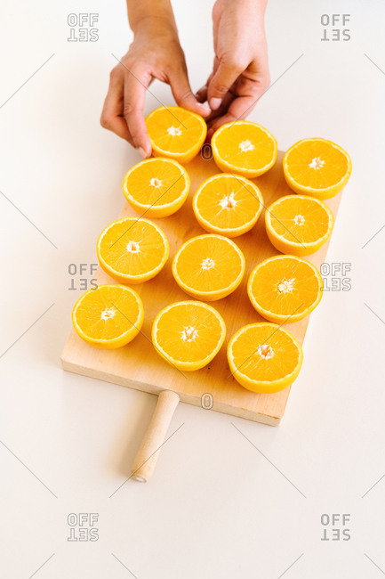 High angle of unrecognizable crop person arranging halves of ripe juicy oranges on wooden chopping board in studio on white background