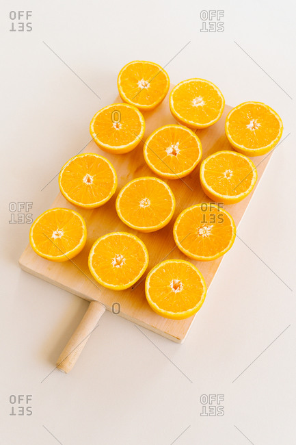 High angle of halves of ripe juicy oranges on wooden chopping board in studio on white background