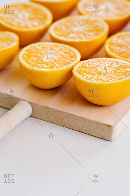 Closeup of halves of ripe juicy oranges on wooden chopping board in studio on white background