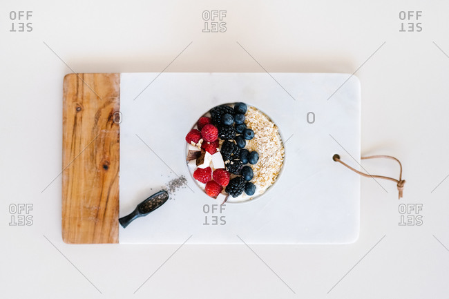 High angle of nutritious bowl with muesli and various berries in bowl placed on table with towel for breakfast in morning
