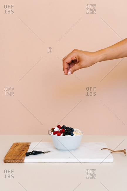 Unrecognizable female pouring delicious coconut flakes in bowl with sweet berries and yogurt placed on table in kitchen for breakfast